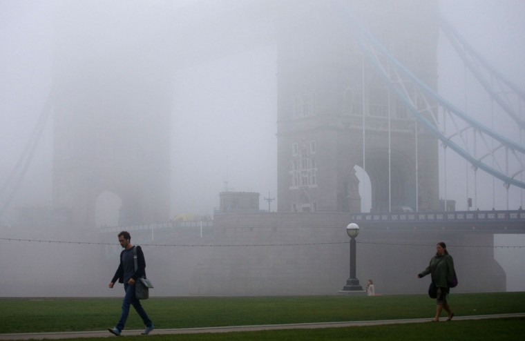 Early morning commuters walk past Tower Bridge shrouded in fog in London on September 24, 2013. (Andrew Cowie/AFP/Getty Images)