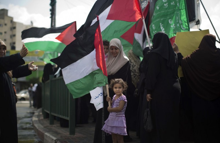 A Palestinian girl holds the national flag during a protest organised by the ruling Islamic Hamas movement in Gaza city on September 24, 2013, amid recent tensions among Palestinians regarding Israel's admittance of visitors to a holy site in Jerusalem's Old City which houses the al-Aqsa mosque and which Jews revere as the vestige of their ancient temples. (Mahmud Hams/AFP/Getty Images)