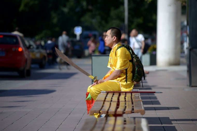 A man training in martial arts rests on a bench along a business street in Beijing on September 24, 2013. The seven-day holiday built around China's National Day on October 1 sees millions of members of China's newly wealthy and mobile middle-class travel locally and abroad. (Wang Zhao/AFP/Getty Images)