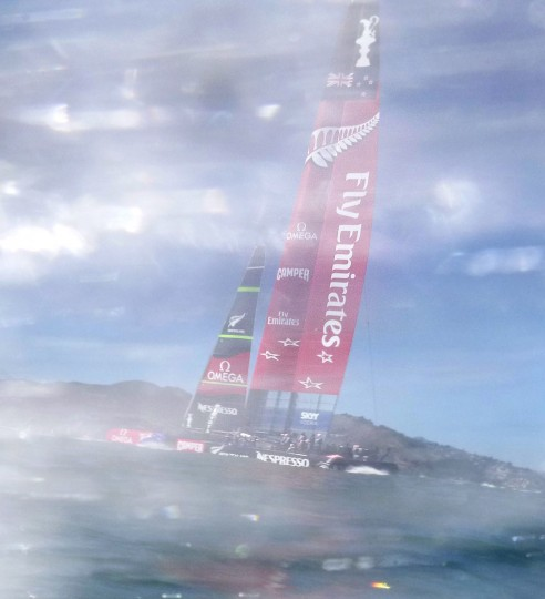 Seen through water spray, Emirates Team New Zealand heads to the start of America's Cup race 18. (Noah Berger / AFP/Getty Images)