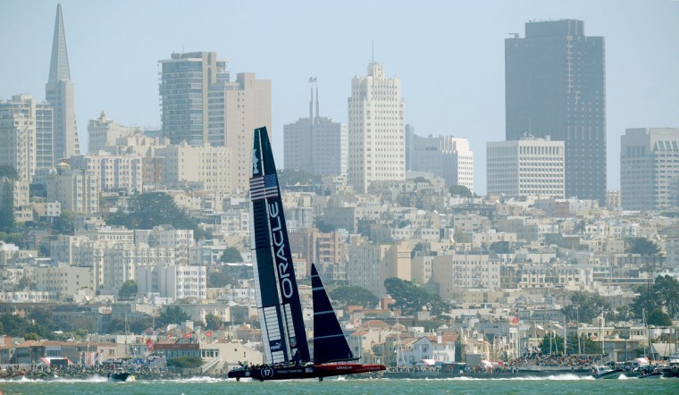 Oracle Team USA passes the San Francisco waterfront while sailing against Emirates Team New Zealand in America's Cup race 17. (Noah Berger / AFP/Getty Images)
