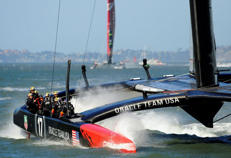 Oracle Team USA splashes down in the water as they pass the finish line to win race 18 of the 34th America's Cup. (Josh Edelson / AFP/Getty Images)