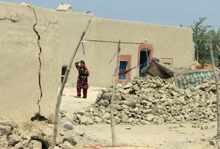 A Pakistani earthquake survivor walks past collapsed mud houses at Labach area, in the earthquake-devastated district of Awaran. (BANARAS KHAN / AFP/Getty Images)
