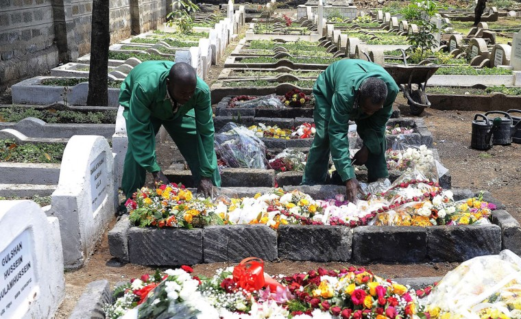 Workers at the Shia Imami Ismailia cemetry arrange flowers on the grave of Kenyan journalist Ruhila Adatia-Sood during her funeral ceremony in Nairobi. Ruhila Adatia-Sood was killed by gunmen at the Westgate Mall attack in Nairobi. (SIMON MAINA / AFP/Getty Images)