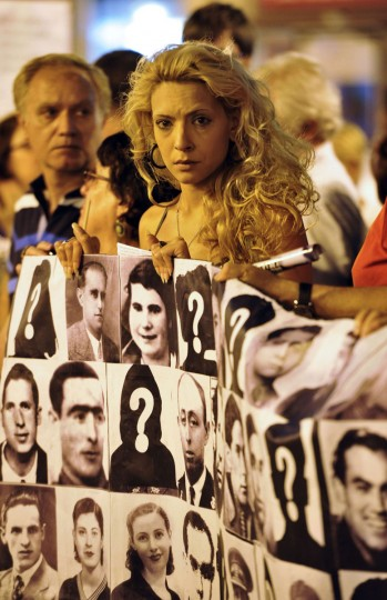 Protesters hold a giant banner with portraits of victims of the dictatorship of General Francisco Franco, during a demonstration in front of the former National Security headquarters at the Puerta del Sol in Madrid. (GERARD JULIEN / AFP/Getty Images)
