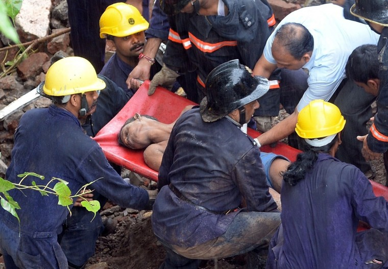 Firefighters and rescue workers bring out a survivor from under the rubble of a collapsed building in Mumbai. A five-story building collapsed in Mumbai at day-break in the latest accident in India's financial capital, with dozens feared trapped inside. (INDRANIL MUKHERJEE / AFP/Getty Images)