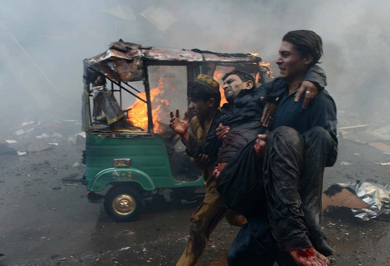 Pakistani men carry an injured blast victim at the site of a bomb explosion in the busy Kissa Khwani market in Peshawar on September 29, 2013. A bomb explosion killed at least 31 people in Pakistan's northwestern city of Peshawar, officials said -- the third deadly strike to hit the city in the last week. (Hasham Ahmed/AFP)