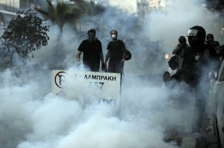 Protesters wear masks to protect themselves from tear gas as they clash with police in the western Athens working-class suburb of Keratsini. (LOUISA GOULIAMAKI / AFP/Getty Images)