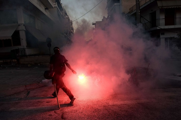 A protestor lights a flare as anti-fascist demonstrators clash with riot police in Athens after a leftist musician was murdered by a suspected neo-Nazi. (ARIS MESSINIS / AFP/Getty Images)