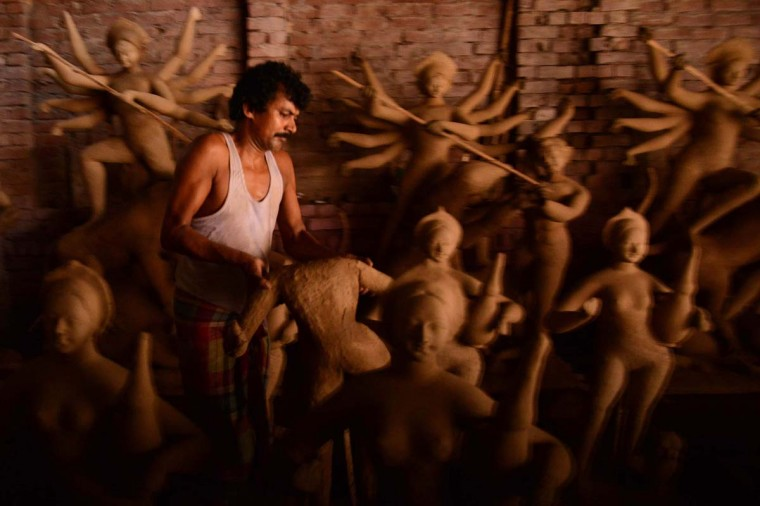 Indian artisan works on a clay idol of the Hindu Goddess Durga in preparation for the forthcoming Hindu festival Durga Puja, in Amritsar on September 30, 2013. The annual five-day Hindu festival worships the goddess Durga, who symbolises power and the triumph of good over evil in Hindu mythology. (Narinder Nanu/AFP)