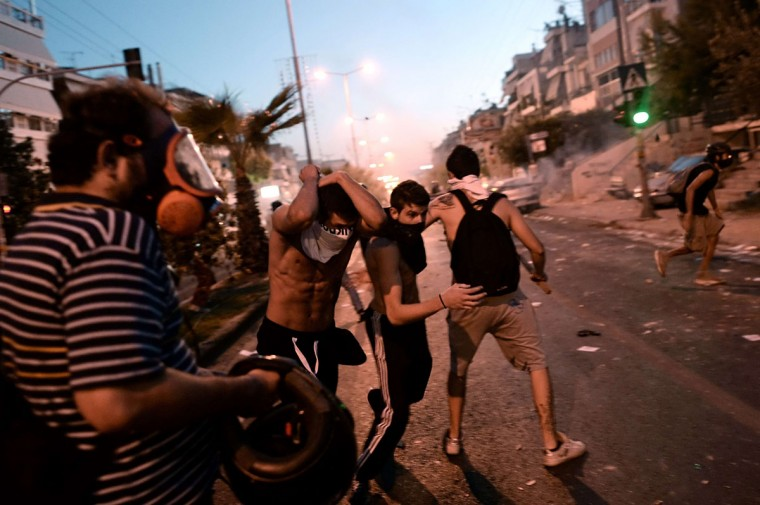 Demonstrators run away from riot police during clashes in Athens after a leftist musician was murdered by a suspected neo-Nazi. (ARIS MESSINIS / AFP/Getty Images)