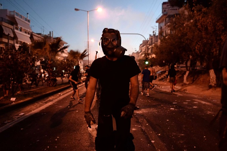 A protester wears a gas mask during clashes with police in the western Athens working class suburb of Keratsini. (ARIS MESSINIS / AFP/Getty Images)