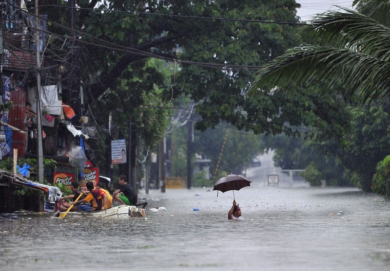 A resident wades through chest-deep floodwaters along a street while his neighbors paddle an improvised life raft in Manila. (TED ALJIBE / AFP/Getty Images)