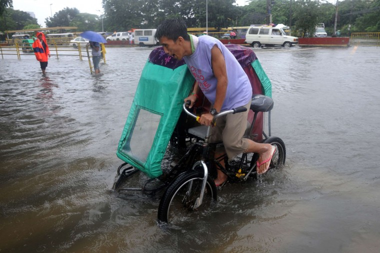 A pedicab driver wades through flooded street in Manila. (NOEL CELIS / AFP/Getty Images)