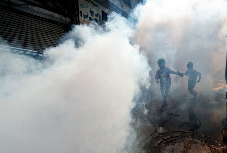 Indian children follow as a municipal corporation worker fumigates the area to prevent mosquitos from breeding in New Delhi. (PRAKASH SINGH / AFP/Getty Images)