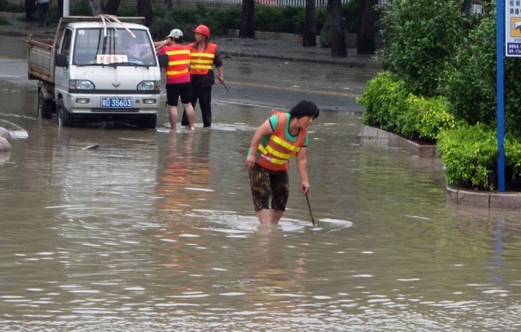 Workers work to drain a flooded street in Shantou, south China's Guangdong province. (Getty Images)