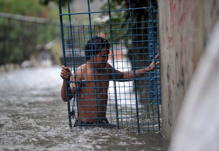 A resident closes the gate of his flooded house at an informal settlers' area in Manila. (TED ALJIBE / AFP/Getty Images)