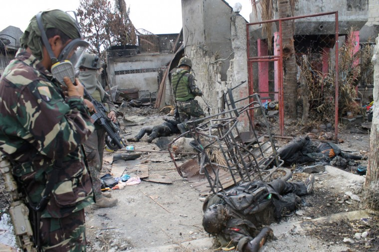Philippine soldiers, wearing gas masks, look at bodies believed to be Muslim rebels next to destroyed houses at the site of heavy fighting during the stand-off between government forces and Moro National Liberation Front (MNLF) rebels in Santa Catalina area of Zamboanga City on the southern island of Mindanao. (FREDERICK ALVAREZ / AFP/Getty Images)