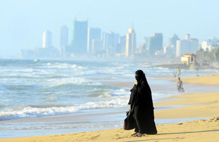 A Sri Lankan Muslim woman walks on the beach in Colombo. Sri Lanka's youth population aged 10 to 19 make up some 15 percent of its 20 million people. (LAKRUWAN WANNIARACHCHI / AFP/Getty Images)