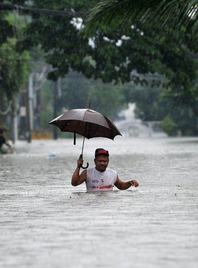A resident wades through chest-deep floodwaters along a street in Manila. (TED ALJIBE / AFP/Getty Images)