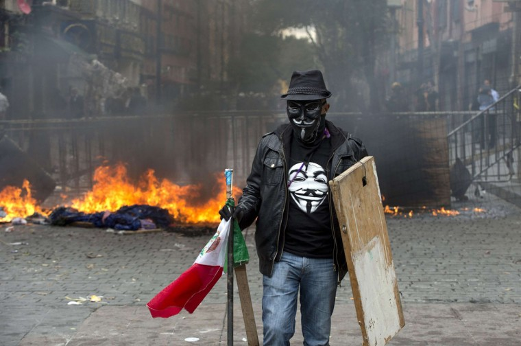 A teacher protesting against education reform stands near a barricade erected against the Mexican Federal Police during a violent eviction of Mexico City's Zocalo Square (Yuri Cortez / AFP/Getty Images)