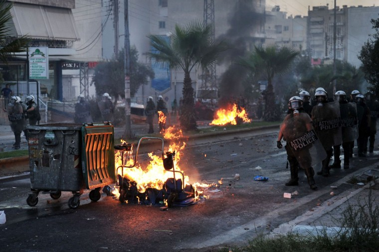 Riot police stand beside burning barricades during clashes with anti-fascist protesters in the western Athens working class suburb of Keratsini. (LOUISA GOULIAMAKI / AFP/Getty Images)