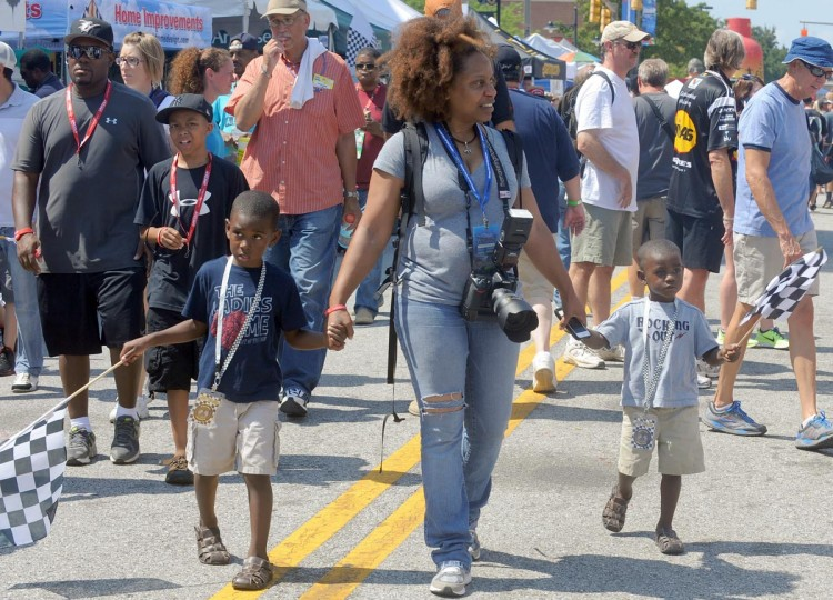 "Tami E. Johnson from Largo holds the hands of her godchildren, Junis ""JJ"" Fletcher, Jr. , 5 and his brother Jayden Flether, 3 as they wave their flags at the Grand Prix of Baltimore 2013. (Algerina Perna/Baltimore Sun)"