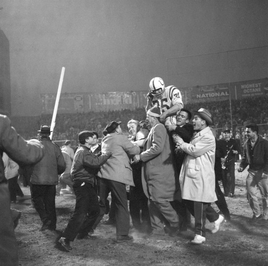 12/28/1958 - Baltimore Colts Alan Ameche victorious, gets carried off the football field by fans after scoring the game winning touchdown vs New York Giants during overtime at Yankee Stadium. Bronx, NY. (Neil Leifer/Sports Illustrated)