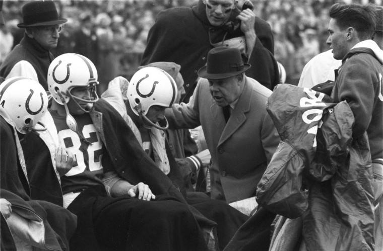 11/6/1960 - Baltimore Colts quarterback Johnny Unitas, center, and head coach Weeb Ewbank, center with hat, on the sidelines during game versus the Green Bay Packers at Memorial Stadium. (Neil Leifer/Sports Illustrated)