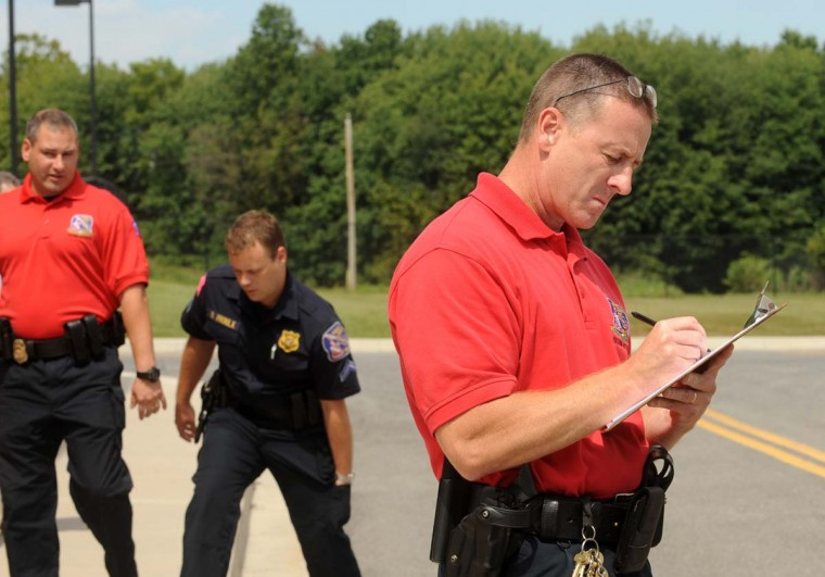 "Sgt. Kevin Costello, right, makes notes on officers' performances as they participate in a training exercise. ""It just gives a feeling that you're actually there,"" beyond what you could do in a classroom, Costello said. ""Psychologically, you know you're in a classroom,"" said Costello. Algerina Perna/Baltimore Sun"