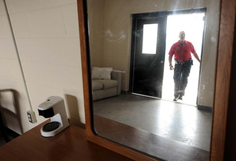 "Lt. Robert Wagner is reflected in a mirror in a simulated hotel room where police officers train on how to respond to various police calls. ""The more realistic you can make training, the better officer you're going to have,"" Wagner said. Algerina Perna/Baltimore Sun"