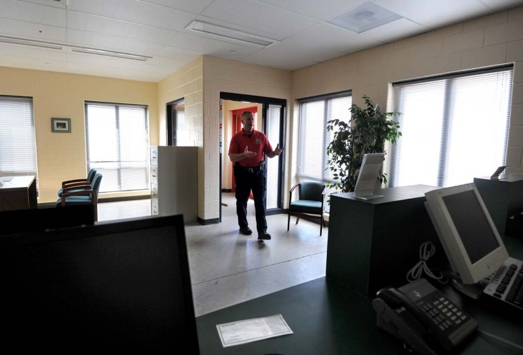 Lt. Robert Wagner shows off the Columbia Bank space that is dressed up pretty much like the real thing inside, down to the little brass-colored FDIC sign on the teller counter and the potted plants. Algerina Perna/Baltimore Sun