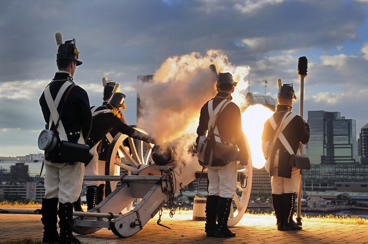 The Corps of Artillery at Fort McHenry are illuminated as they fire a Napoleonic six-pound field piece as members of Fort McHenry usher in Defenders' Day celebration on Federal Hill to start the weekend Friday, Sep 13, 2013. (Karl Merton Ferron/Baltimore Sun)
