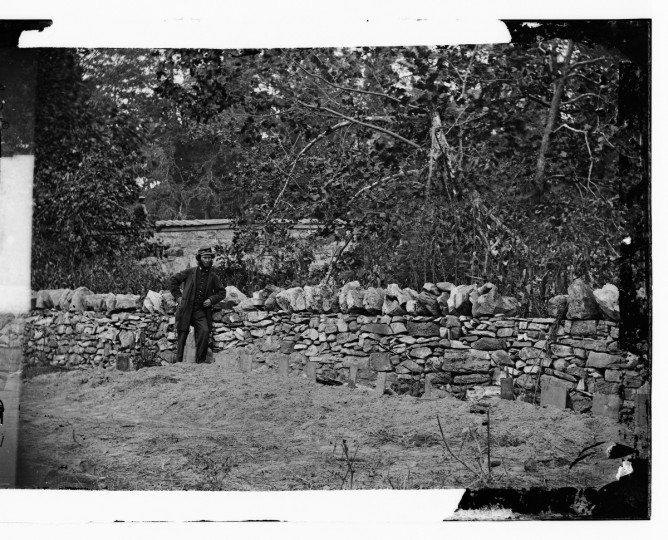 "The right portion of a 3-D photo taken by Alexander Gardner that he labeled ""Soldier standing at graves of Federal soldiers, along stone fence, at Burnside Bridge, Antietam, Maryland. "" (Alexander Gardner/Courtesy Library of Congress)"