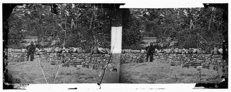 "A 3-D photo taken by Alexander Gardner that he labeled ""Soldier standing at graves of Federal soldiers, along stone fence, at Burnside Bridge, Antietam, Maryland."" (Alexander Gardner/Courtesy Library of Congress)"