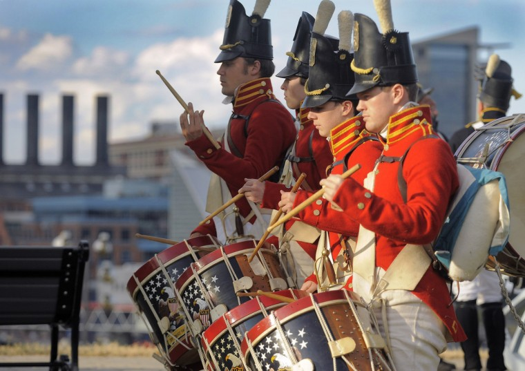 From foreground to background, Phillip Rogers, Austin Rogers, Dan Morrison, and Nick Ross of Fort McHenry Guard play with the inner harbor as a backdrop, as members of Fort McHenry usher in Defenders' Day celebration on Federal Hill to start the weekend Friday, Sep 13, 2013. (Karl Merton Ferron/Baltimore Sun)