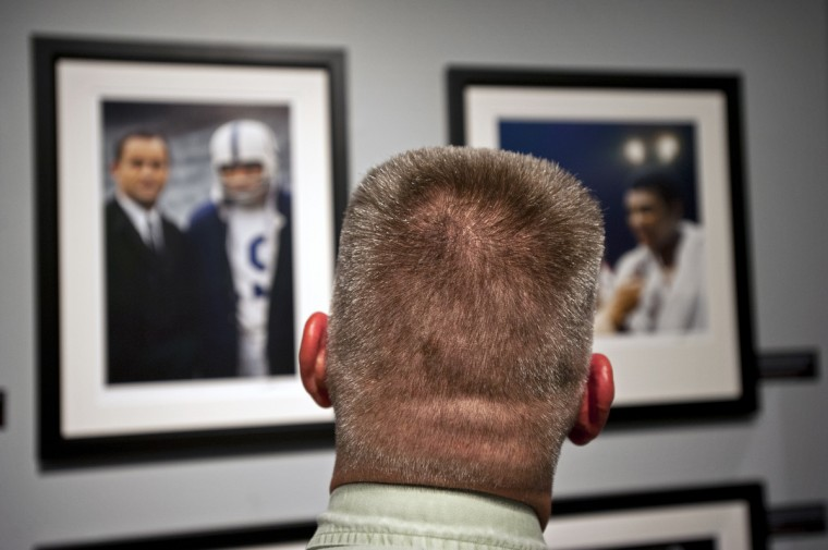 "A spectator looks at a photograph of Don Shula and Johnny Unitas at the opening to Sports Legends Museum's ""Images We Remember -The World of Neil Leifer"" exhibit which will be on display until October 2014. I(Christopher T. Assaf/Baltimore Sun)"