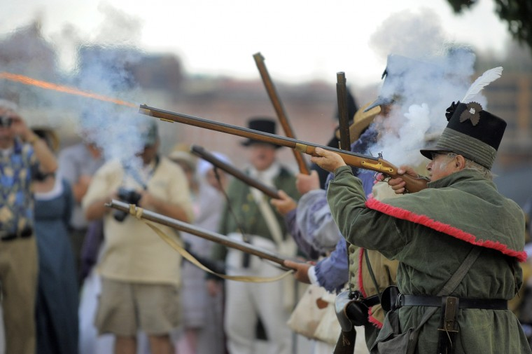 Aleksandras Radzius fires his weapon while standing with the First Baltimore Rifle Company (snipers of the time), as members of Fort McHenry usher in Defenders' Day celebration on Federal Hill to start the weekend Friday, Sep 13, 2013. (Karl Merton Ferron/Baltimore Sun)