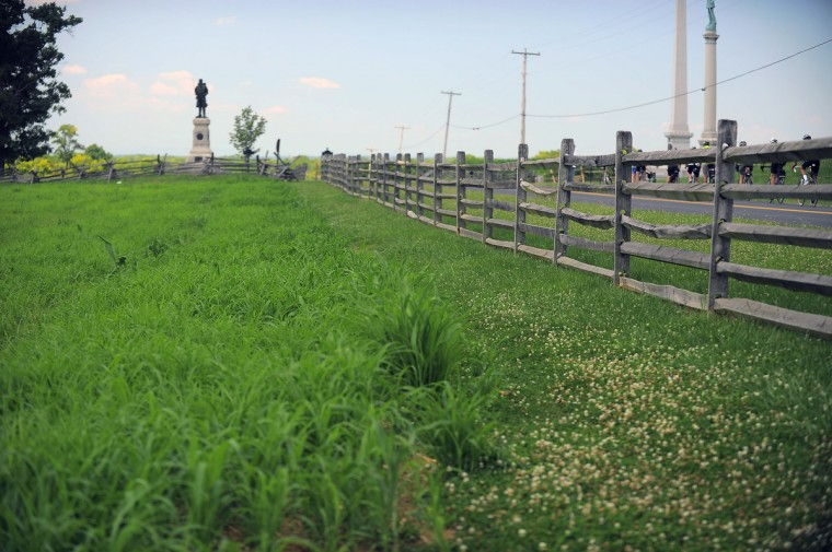 "A modern-day view of the replica wooden fence along Dunker Church Road (once called Hagerstown Turnpike) as a throng of bike riders stop on the road at Antietam National Battlefield. The angle, mimicking an 1862 stereo (or, 3-D) image called ""Confederate dead by a fence on the Hagerstown road"" -one of two of the most iconic images of Antietam. (Karl Merton Ferron/Baltimore Sun)"