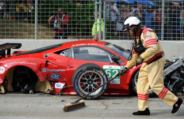 A safely crew member sweeps debris next to the damaged Risi Competizione Ferarri after a massive pileup at the start of the ALMS race Saturday, Aug. 31, 2013. (Jerry Jackson/Baltimore Sun)