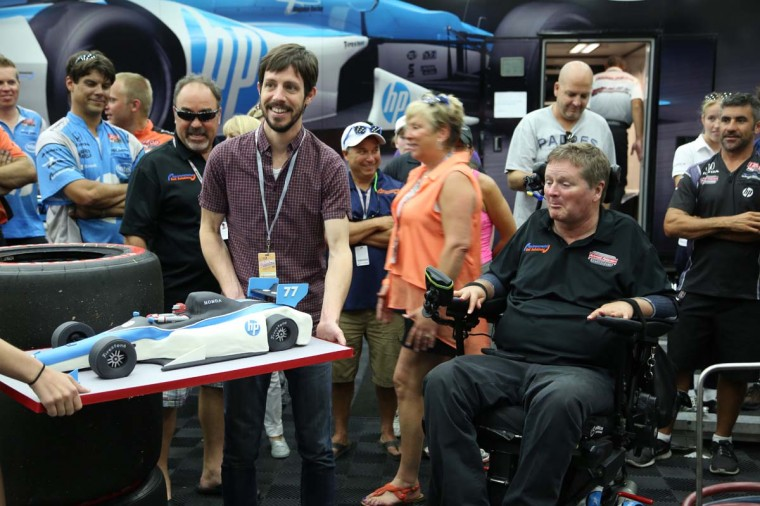 Sam Schmidt (right), owner of IZOD IndyCar Series team Schmidt Peterson Motorsports, is presented with a surprise racecar- shaped birthday cake from Charm City Cakes Saturday in the IZOD IndyCar Series paddock at the Grand Prix of Baltimore. Schmidt became a quadriplegic in 2001 after a testing crash at Walt Disney World Speedway. (Kaitlin Newman/Baltimore Sun)