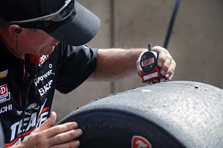 A pitcrew member of IZOD Indycar Series' Team Penske checks the tire tread level of a tire after it was used during the last practice by driver Helio Castroneves before racing in the Grand Prix of Baltimore Sunday, Sept. 1, 2013. (Kenneth K. Lam/Baltimore Sun)