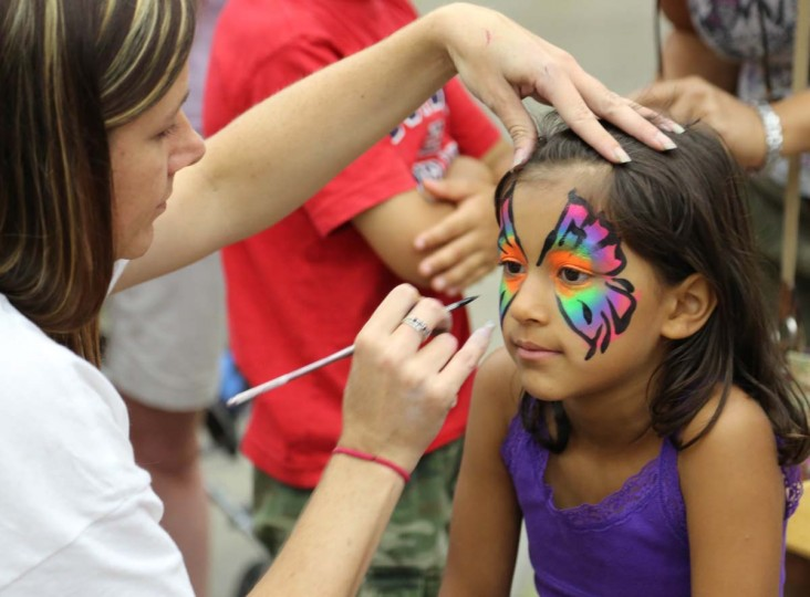 Mayah Simon, 6, from Wallkill, N.Y., has her face painted in the family fun zone at the Baltimore Grand Prix on Saturday, Aug. 31, 2013. (Kaitlin Newman/Baltimore Sun)