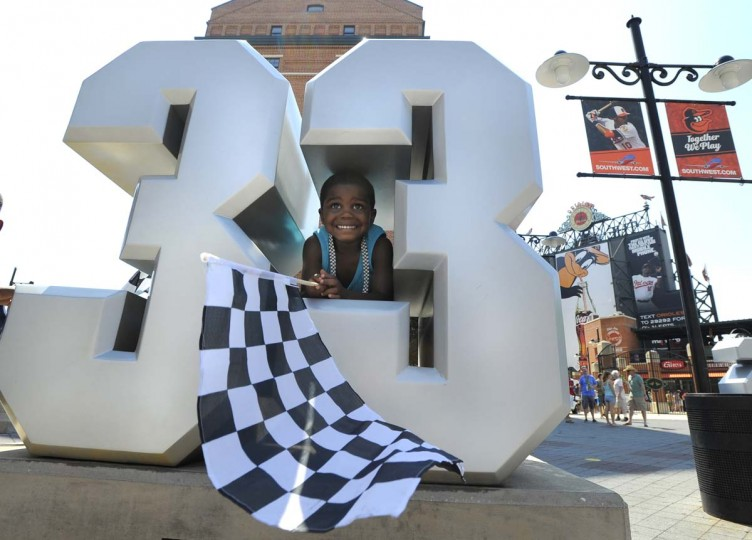Dorian Jordan, 3, of Clinton, Md. waves his checkered flag near Camden Yards and the the #33 of Oriole great Eddie Murray. Grand Prix of Baltimore on Sept. 1, 2013. (Lloyd Fox/Baltimore Sun)