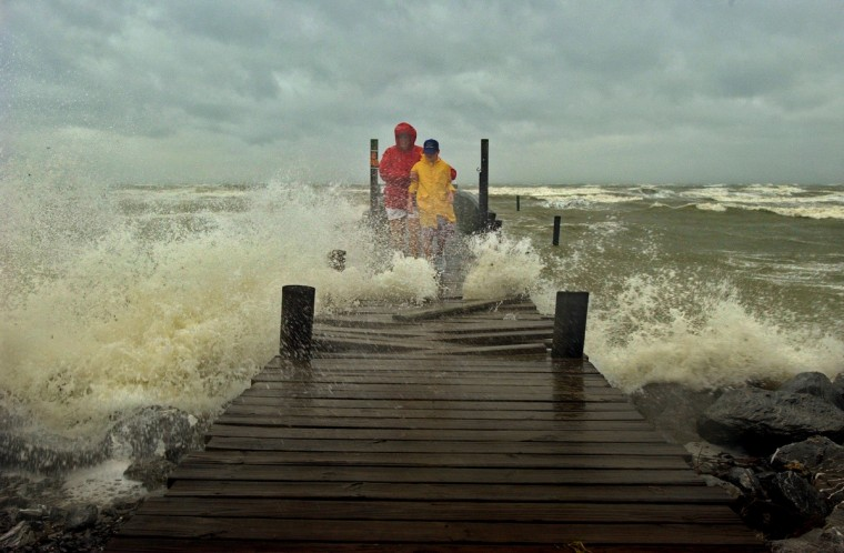 Elise Feldman stands by her son Josh Feldman, 11 of Leonardtown, MD, cautiously watching their footing as the pier breaks up from the force of the waves pounding the boards loose as Hurricane Isabel slams into the eastern seaboard and into the mid-Atlantic states September 18, 2003. (Karl Merton Ferron/Baltimore Sun)