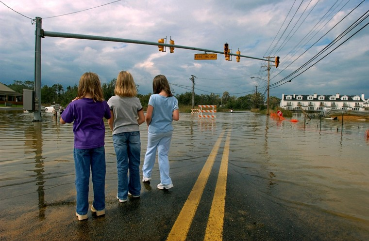 From left, Nicole Randolph, 7, sister Megan Randolph, 9 and neighbor Bethany Aoldhman, 8, stand at the water's edge of closed Md. Route 261 at Chesapeake Beach., September 19, 2003. High water prompted closure of the road that leads northward to North Beach. (Karl Merton Ferron/Baltimore Sun)
