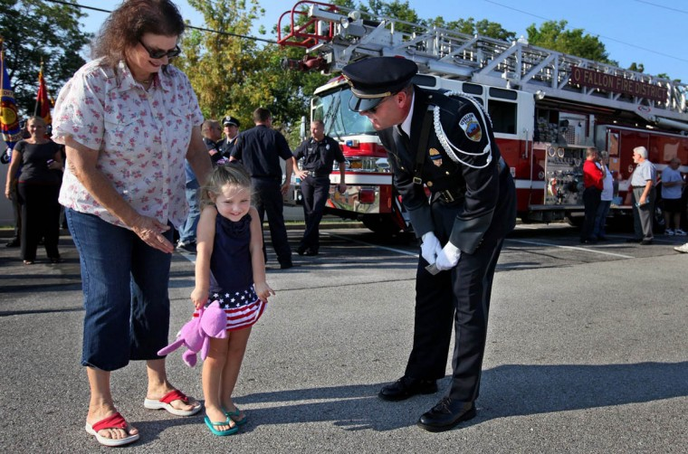 Jeanne Tallman, left, escorts her granddaughter Whitney Weeks, 3, as she hands a coloring she did to O'Fallon police officer Mike Plum after a ceremony honoring first responders in O'Fallon, Missouri, Wednesday, September 11, 2013. (David Carson/St. Louis Post-Dispatch/MCT)