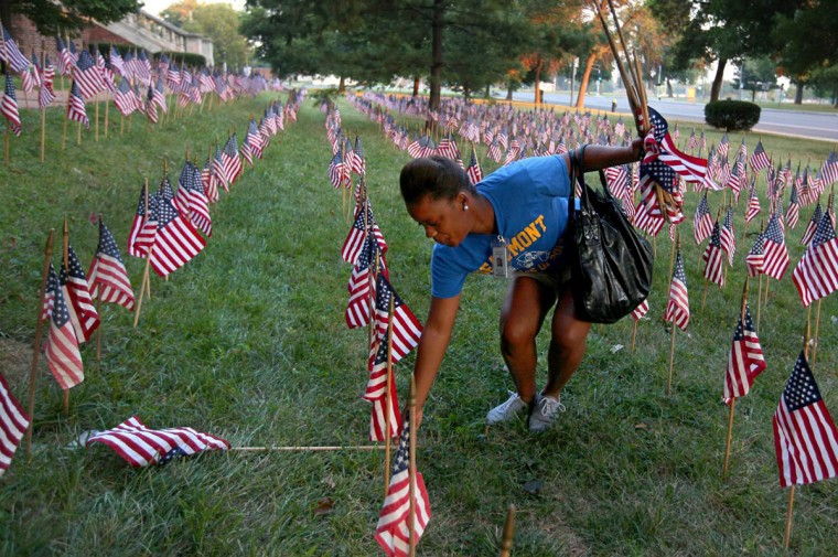 Crystal Eubanks, a senior JROTC student at Beaumont High School, picks up flags that were knocked down over night outside the school, Wednesday, September 11, 2013. On Tuesday night ROTC students put up about 3,000 flags as tribute to the people who lost their lives in the attacks of Sept. 11, 2001. (David Carson/St. Louis Post-Dispatch/MCT)