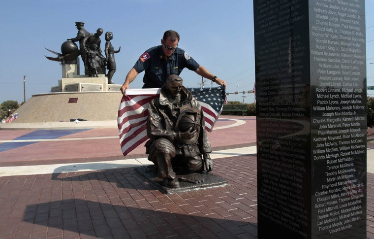 Grapevine Fire Department Captain/Assistant Fire Marshal Craig Reed replaces a flag around a statue of a firefighter after photographing the statue at The Flight Crew Memorial in Grapevine, Texas, Wednesday, September 11, 2013, on the 12th anniversary of the 9/11 attacks. (Ian McVea/Fort Worth Star-Telegram/MCT)