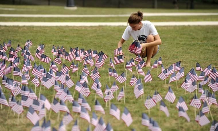 Penn State student Allie Coleman plants U.S. flags on Old Main lawn as the university played host to a ceremony Wednesday, September 11, 2013, in State College, Pensylvania. The event included the planting of 2,996 American flags to remember each lost l